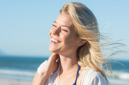Photo for Portrait of laughing woman touching her hair. Cheerful attractive woman enjoying at beach. Joyous woman at sea shore laughing. Young blonde at sea shore with a toothy smile. - Royalty Free Image