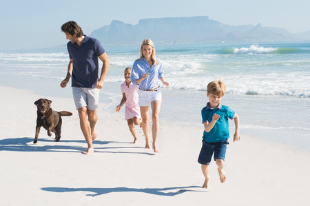 Foto de Family playing with pet on the beach. Happy beautiful family running at beach with pet dog. Smiling parents with son and daughter having fun at seaside. - Imagen libre de derechos
