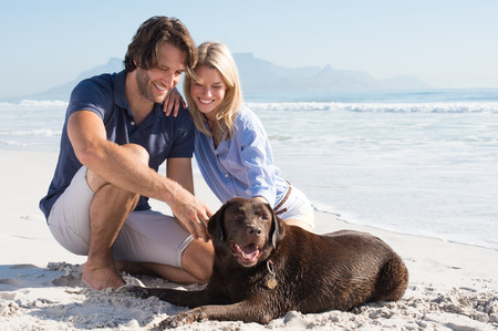 Photo pour Cheerful couple at beach playing with labrador retriever. Couple relaxing at beach with their pet. Happy couple with their dog at the beach on a sunny day. - image libre de droit