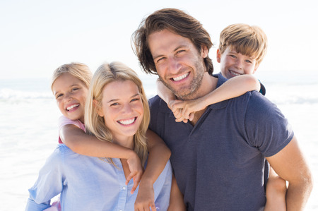 Foto de Parents giving piggyback ride to kids at beach. Close up of smiling family having fun at summer vacation. Portrait of happy family looking at camera at beach. - Imagen libre de derechos