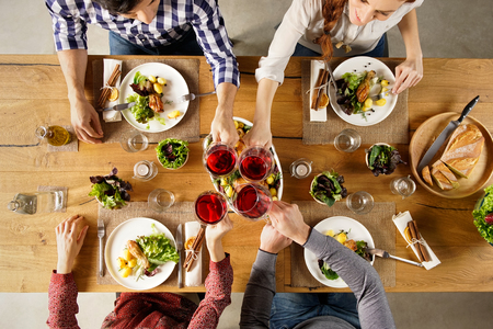 Photo for Top view of group of friends raising a toast post lunch. High angle view of happy men and women celebrating at home with red wine. Close up shot of friends toasting glasses of red wine in a party. - Royalty Free Image