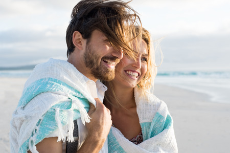 Photo pour Happy couple wrapped up in blanket at beach. Young couple wrapped in towel on beach. Smiling couple at beach enjoying view of the sea during sunset. - image libre de droit