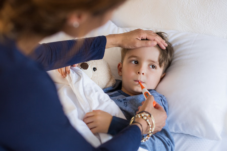 Sick boy with thermometer laying in bed and mother hand taking temperature. Mother checking temperature of her sick son who has thermometer in his mouth. Sick child with fever and illness while resting in bed.