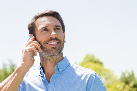 Photo pour Happy man talking over phone on a bright sunny day and looking up. Smiling mature man using mobile phone outdoor. Portrait of a man in a conversation through mobile phone. - image libre de droit