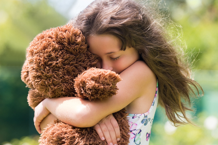 Photo pour Emotional girl hugging her teddy bear. Young cute girl embracing her brown fur teddy bear. Little girl in love with her stuff toy. - image libre de droit