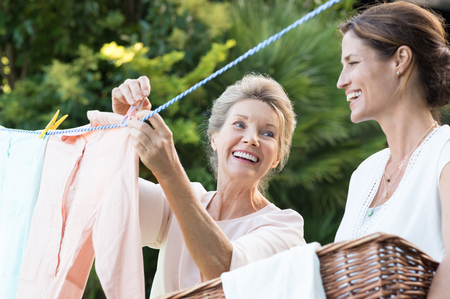 Photo for Older mother and young daughter hanging clothes outdoor to dry. Smiling daughter helping mother with laundry. Cheerful mother and daughter in conversation while hanging clothes outside. - Royalty Free Image