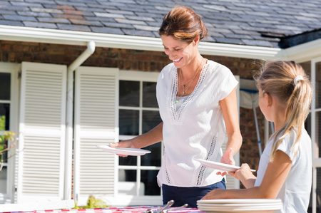 Photo pour Cheerful young mother arranging plates on dining table outside house. Daughter helping mother arrange the table in the courtyard. Daughter giving plates to mother. - image libre de droit