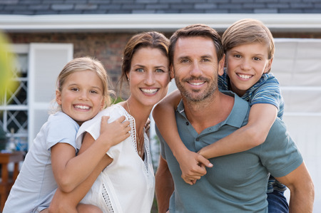 Photo pour Parents giving piggyback ride to children. Happy mother and father with son and daughter looking at camera outside house. Portrait of happy couple standing carrying on shoulder their children. - image libre de droit