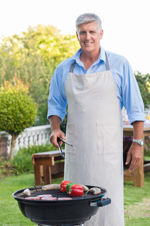 Senior man wearing apron and cooking food in the garden house. Happy grandfather barbequing outdoors for his family. Portrait of old man cooking bbq and looking at camera.