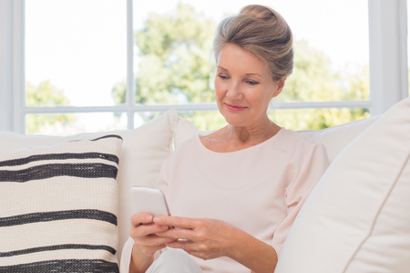 Foto per Senior woman using mobile phone while sitting on sofa. Older woman sitting on sofa and texting a phone message. Portrait of a beautiful elderly woman learning to use smartphone. - Immagine Royalty Free