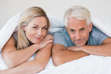 Foto de Senior romantic couple under a white duvet in the bed. Happy mature couple lying down in their bed and looking at camera. Retired man and smiling woman having fun lying on bed at home. - Imagen libre de derechos