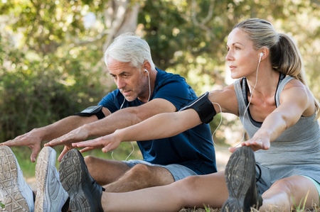Foto de Mature couple stretching at park and listening to music. Athletic senior couple exercising together outdoor. Fit senior runners stretching before running outdoors. - Imagen libre de derechos