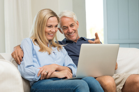 Photo for Mature man and his wife working with laptop at home. Senior couple using ecommerce in internet with computer. Cheerful senior couple sitting on sofa at home and using laptop. - Royalty Free Image
