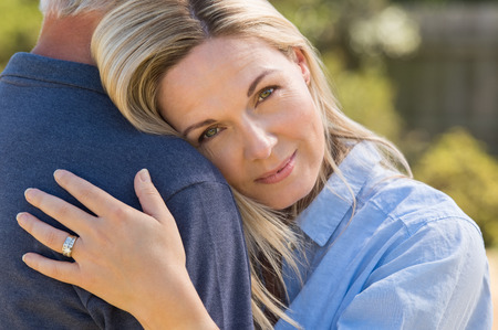 Foto de Close up face of a loving woman embracing senior man. Portrait face of mature romantic couple hugging outdoor. Closeup face of senior woman embracing husband in park. - Imagen libre de derechos