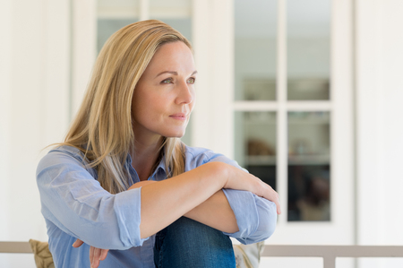 Foto de Woman sitting outside the house and thinking about her new idea. Pensive mid woman relaxing at home on a holiday. Portrait of mature woman planning her future. - Imagen libre de derechos