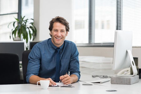 Photo for Cheerful young businessman working at desk in office. Successful business man sitting in office with a cup of coffee. Portrait of happy young businessman laughing and looking at camera. - Royalty Free Image