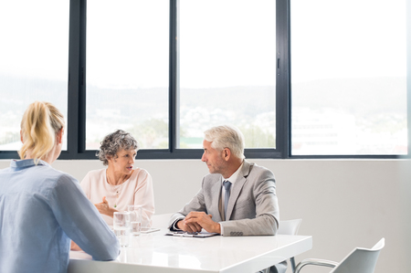 Business executive conducting job interview with young woman. Personnel managers conducting job interview talking amongst themselves about their decision. Team of human resources conducting interviews at office.