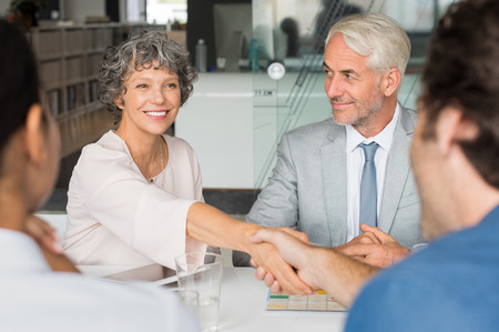 Close up of a cheerful senior business woman shaking hands with businessman. Business people shaking hands in meeting. Handshake between mature leadership and young business man.の写真素材
