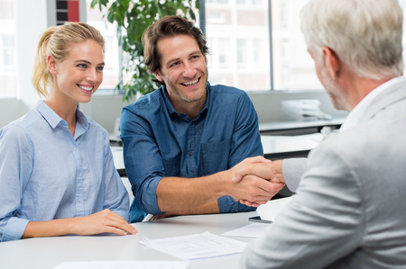 Photo pour Handshake of a senior financial advisor with a young man and his girlfriend. Businessman handshake with couple during meeting signing agreement. Real estate agent shaking hands with happy smiling couple. - image libre de droit