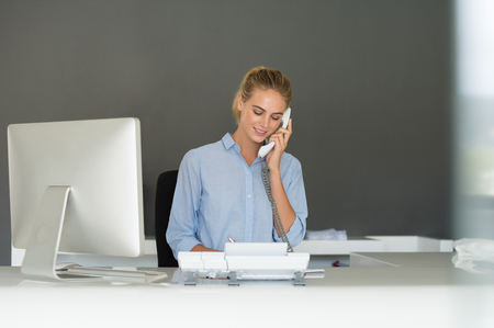 Smiling receptionist using telephone at desk. Customer service representative making phone call. Beautiful businesswoman talking on telephone at workplace. Beautiful young secretary talking on the phone at office.