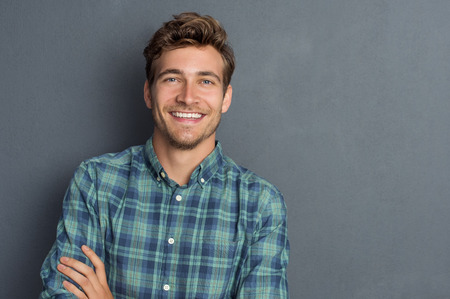 Young handsome man leaning against grey wall with arms crossed. Cheerful man laughing and looking at camera with a big grin. Portrait of a happy young man standing with crossed arms over grey background.