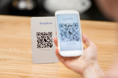 Foto de Closeup of a hand holding phone and scanning qr code. Woman hand paying with qr code. Close up of customer hand making payment through smart phone and scan code. - Imagen libre de derechos