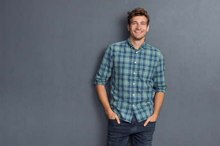 Foto de Handsome young man on grey background looking at camera. Portrait of laughing young man with hands in pockets leaning against grey wall. Happy guy smiling. - Imagen libre de derechos