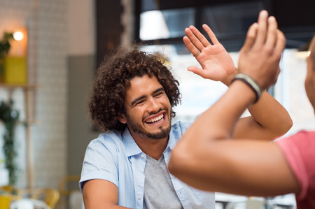 Photo pour Portrait of friends giving high five at cafe while having lunch. Young guys friends giving a high five, slapping each others hand in congratulations while sitting in cafeteria. - image libre de droit