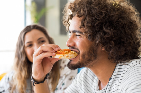 Photo pour Close up face of a young african man eating a pizza in a coffee shop. Happy guy with friends enjoying brunch in a cafeteria. Portrait of a multiethnic young man biting pizza. - image libre de droit