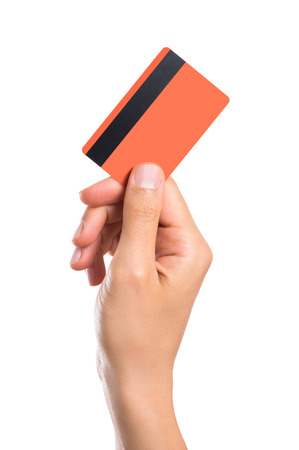Foto de Hand holding credit card isolated on white background. Close up of a man hand holding up a creditcard. Male hand showing orange credit card with magnetic strip. - Imagen libre de derechos