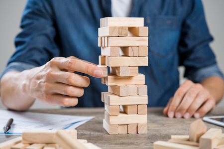 Photo pour Businessman thinking about new challenge. Close up of hand of man taking a piece of building wooden bricks. Businessman trying to find a solution to problem by building with wooden bricks. Risk and strategy concept. - image libre de droit