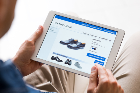 Foto de Young man looking at shoes online. Man looking at various shoes options over internet through digital tablet. Casual man makes online shopping at home with digital tablet. - Imagen libre de derechos