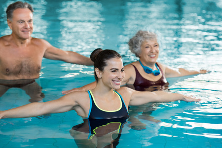 Foto de Smiling fitness class doing aqua aerobics in swimming pool. Smiling young woman with senior couple stretching arms in swimming pool while doing aqua aerobics. Fit mature man and old woman exercising in swimming pool with young woman. - Imagen libre de derechos