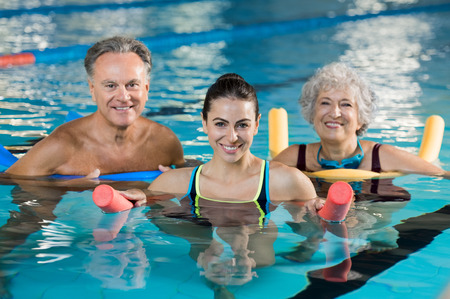 Happy mature man and old woman doing aqua aerobics with foam rollers in swimming pool. Senior couple smiling with swim noodles doing aqua fitness. Smiling young trainer with mature class doing aqua gym fitness.