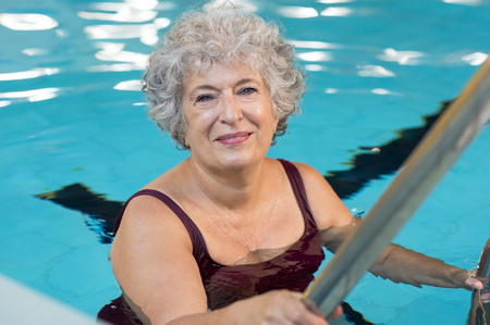 Foto de Smiling active senior woman entering in a swimming pool. Smiling old woman looking at camera before the water aerobics lesson. Happy mature woman ready to swim. - Imagen libre de derechos