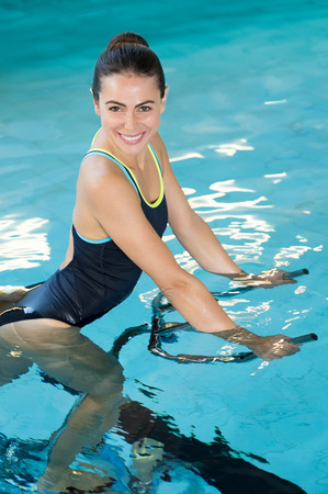 Fit smiling woman cycling on aqua bike in swimming pool. Smiling young woman using under water exercise bike in the swimming pool. Happy sporty girl doing exercise bikes in swimming pool and looking at camera.