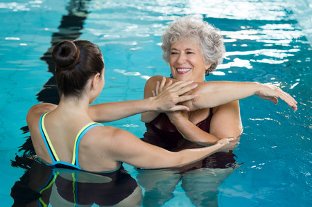 Photo for Young trainer helping senior woman in aqua aerobics. Senior retired woman staying fit by aqua aerobics in swimming pool. Happy old woman stretching in swimming pool with young trainer. - Royalty Free Image