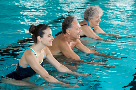 Foto de Happy smiling mature man and old woman cycling on a swimming bike in swimming pool. Happy and healthy senior people enjoying swimming with young woman. Fitness class doing aqua aerobics on exercise bikes in a swimming pool. - Imagen libre de derechos