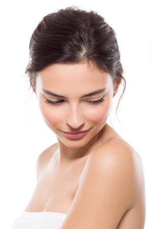 Foto de Young beautiful woman with perfect skin looking down. Close up face of beauty young woman. Young beautiful woman feeling shy isolated on white background. Wellness and skin care concept. - Imagen libre de derechos