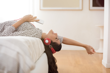 Happy young woman with headphones listening to music while lying on bed at home. Beautiful brunette girl with headphones relaxing on the bed. Smiling woman enjoying music on headphones holding phone and stretching out arms in bedroom.