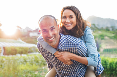 Foto de Happy mature couple enjoying outdoors during sunset. Smiling woman piggyback on her man while looking at camera. Portrait of middle aged man carrying on shoulder his wife. - Imagen libre de derechos