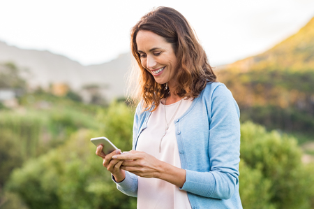 Foto de Mature happy woman using cellphone at park. Smiling woman reading message on smartphone. Brunette latin woman typing a message on her telephone after receiving an email. - Imagen libre de derechos