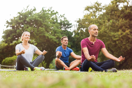 Group of middle aged people doing yoga sitting on grass. Three people practicing meditation and yoga at park on a bright morning. Mature woman and two mid men meditating together in a lotus position.の写真素材