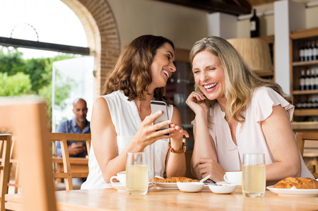 Cheerful mature women enjoying a funny video on mobile phone. Mature friends reading a funny message over smartphone. Mid woman showing a cellphone to her friend while laughing over breakfast.の写真素材