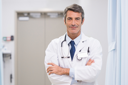 Photo pour Portrait of smiling doctor with stethoscope around his neck at medical clinic. Happy smiling senior doctor at hospital lobby. Mature man feeling confident after a major operation and looking at camera.  - image libre de droit