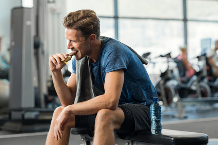Foto de Sweaty young man eating energy bar at gym. Handsome mid guy enjoying chocolate after a heavy workout in fitness studio. Fit man biting a snack and resting on bench. - Imagen libre de derechos