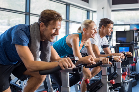 Group of smiling friends at gym exercising on stationary bike. Happy cheerful athletes training on exercise bike. Young men and woman working out at spinning class in the gym.の写真素材
