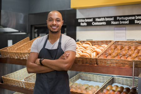 Photo pour Smiling baker man standing with fresh bread at bakery. Happy african man standing with crossed arms at counter in bake shop and looking at camera. Satisfied baker with breads in background. - image libre de droit