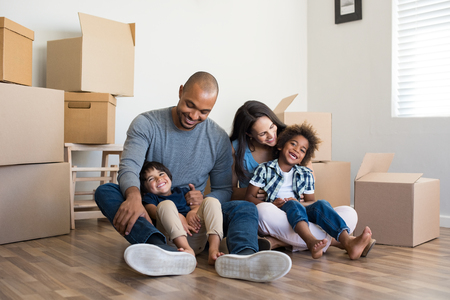 Happy family with two children having fun at new home. Young multiethnic parents with two sons in their new house with cardboard boxes. Smiling little boys sitting on floor with mother and dad.の写真素材