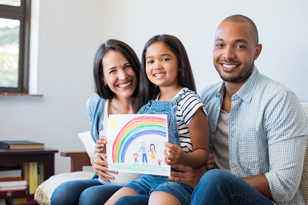 Photo pour Smiling daughter showing painting of happy family with parents and beautiful rainbow. Happy child showing drawing of family with little brother. Cheerful pregnant woman with her family looking at camera. - image libre de droit